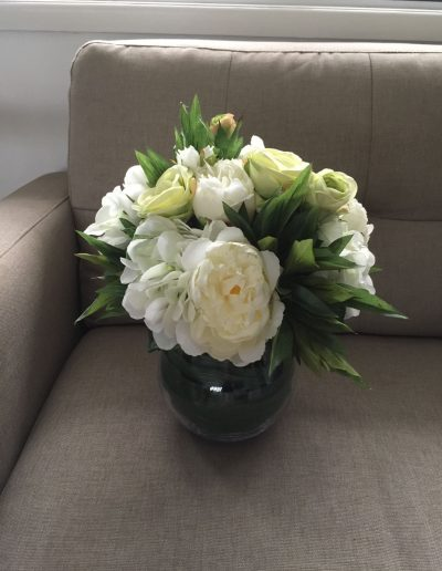 Peonies and green roses in glass vase